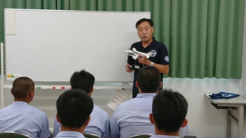 -フライトシミュレータ操縦前に説明をおこなう勝又明志准教授-